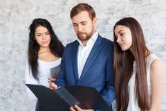 Drei Büroangestellte, überprüfen etwas in einem Ordner mit Dokumenten Lizenzfreies Stockbild