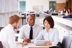 Drei Bürokollegen in einer zufälligen Teambesprechung Lizenzfreie Stockfotos