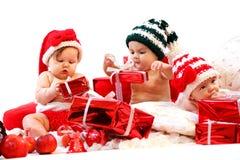 Drei Babys in Weihnachtskostümen, die mit Geschenken spielen Lizenzfreies Stockbild