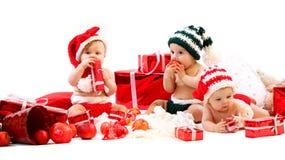 Drei Babys in Weihnachtskostümen, die mit Geschenken spielen Stockfotos
