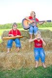Drei Bauernhofmädchen, die Instrumente spielen. Stockfoto