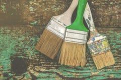 Drei benutzte Malerpinsel auf rustikalem hölzernem Brett Stockfotos
