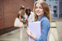 Drei beschäftigte Studenten auf dem Campus Lizenzfreie Stockfotos