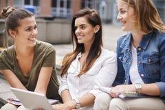 Drei beschäftigte Studenten auf dem Campus Stockbild