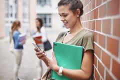 Drei beschäftigte Studenten auf dem Campus Lizenzfreies Stockfoto