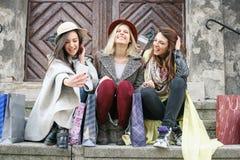 Drei beste Freunde, die nach dem Einkauf genießen Stockfotografie