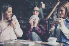 Drei beste Freunde im Café, das zusammen Spielkarten spielt C lizenzfreies stockbild