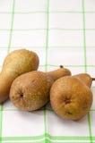 Drei Birnen auf einem Geschirrtuch Stockfotos