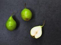 Drei Birnen auf grauem Hintergrund Lizenzfreie Stockfotos
