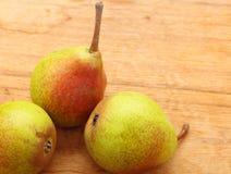 Drei Birnenfrüchte auf Holztischhintergrund Lizenzfreie Stockfotos