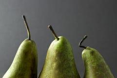 Drei Birnenoberteile und -stiele auf einem dunklen Hintergrund Lizenzfreies Stockfoto