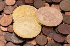 Drei Bitcoins, das auf einen Stapel von alten Kupfermünzen des Eurocents legt Stockfoto