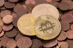 Drei Bitcoins, das auf einen Stapel von Kupfermünzen des Eurocents legt Stockfotografie