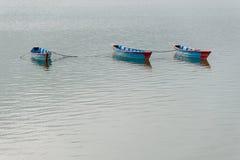 Drei blaue Boote auf Phewa See in Pokhara Lizenzfreies Stockbild