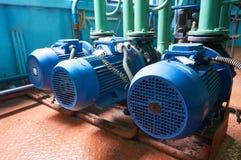 Drei blaue Elektromotoren mit Pumpen schlossen an grüne Rohre an Stockbild