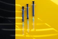 Drei blaue Spritzen liegen auf einer gelben und schwarzen Oberfläche in der Sonne stockfotografie