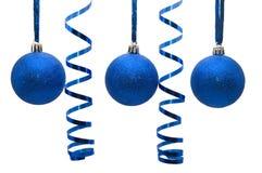 Drei blaue Weihnachtskugeln mit lockigem Farbband Lizenzfreie Stockfotografie