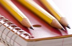 Drei Bleistifte auf Notizbuch Lizenzfreies Stockbild