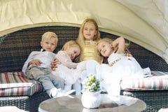 Drei blonde seasters und ein Bruder, die auf Rattansofa sitzen Sonniger Tag Kind-` s Partei an einem Restaurant auf der Straße Stockfotos