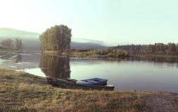 Drei Boote auf dem Ufer von ruhigem Fluss im Sommer Stockfotografie