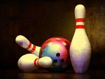 Drei Bowlingspiel-Stifte und eine Bowlingspiel-Kugel Lizenzfreies Stockfoto