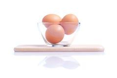 Drei braune Eier auf einem kleinen Schneidebrett lokalisiert auf Weißrückseite Lizenzfreies Stockbild