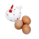 Drei braune Eier mit einer würdevollen keramischen Henne Lizenzfreie Stockfotos