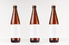 Drei braune NRW-Bierflaschen 500ml mit leerem weißem Aufkleber auf weißem hölzernem Brett, verspotten oben Stockfotos