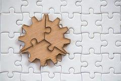 Drei braune Stücke des Puzzlespiels auf einem weißen zackigen Hintergrund, letztes Stück des Puzzlen, zum des Auftrags, Geschäfts stockbild