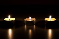 Drei brennende Kerzen in der Dunkelheit Lizenzfreies Stockfoto
