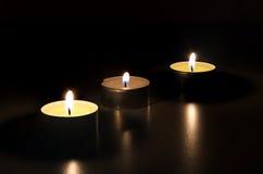 Drei brennende Kerzen in der Dunkelheit Lizenzfreies Stockbild