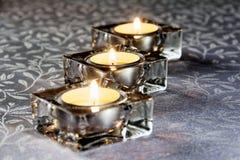 Drei brennende Kerzen im Glas auf einer weißen Tischdecke Lizenzfreies Stockfoto