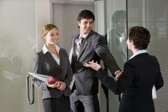 Drei Büroangestellte, die an der Tür des Sitzungssaals plaudern Stockfotografie