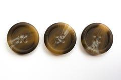 Drei Brown-Plastikknöpfe lokalisiert auf Weiß Lizenzfreies Stockfoto