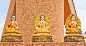 Drei Buddha-Statue, die auf einer Wand sitzt stockfotografie