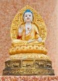 Drei Buddha-Statue, die auf einer Wand sitzt stockfotos