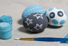 Drei bunte Eier auf einer Tabelle mit einer Bürste und Farben Stockbild