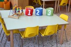 Drei bunte Gläser mit gezogenen Zahlen auf der Schultabelle Stockfotografie