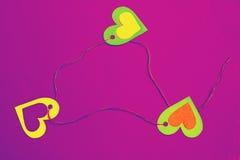 Drei bunte Herzen in einem Dreieck - Konzeptdreiecksverhältnis Stockfotos