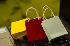 Drei bunte Papiereinkaufstaschen auf einer Laptoptastatur Ideen a Stockfotos