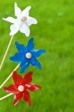 Drei bunte Pinwheels gegen Gras-Hintergrund lizenzfreie stockfotografie