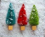 Drei bunte Weihnachtsbäume im Schnee stockfotos