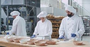 Drei charismatisch und stilvolle Bäcker Frau und Männer, die schwer mit Teigherstellungsstücken zu backendem Brot arbeiten Zeitlu stock video footage