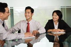 Drei chinesische Wirtschaftler in einer Sitzung Lizenzfreies Stockfoto