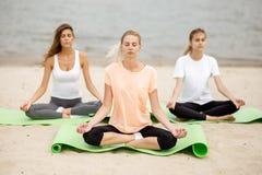 Drei dünne junge Mädchen sitzen in einem Yoga aufwirft mit schließenden Augen auf Matten auf sandigem Strand nahe bei dem Fluss a stockfoto