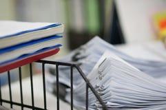 Drei des Berichtsnotizbuches auf schwarzem Regalgestell und des Stapels der weißen Datenpapiere bedecken stockfotos