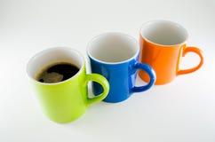 Drei diagonale Becher mit Kaffeetasse in der Mitte Lizenzfreies Stockbild
