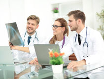 Drei Doktoren, die aufmerksam Röntgenstrahl betrachten und es besprechen Stockfoto