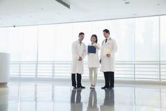 Drei Doktoren, die einem Dokument im Krankenhaus, in voller Länge zurücktreten und betrachten lizenzfreie stockfotos