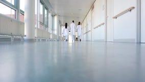 Drei Doktoren, die hinunter einen Korridor im Krankenhaus gehen stock video